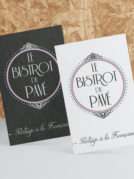 Deux cartes de visite posées contre une planche en bois du Bistrot du Pavé