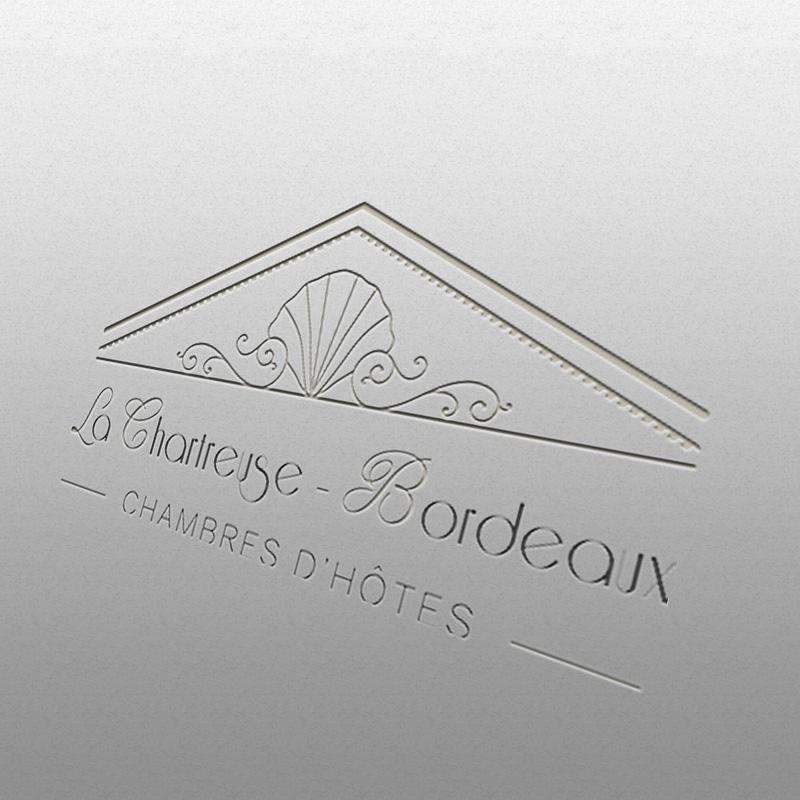 Logo La Chartreuse Bordeaux gravé sur un mur blanc