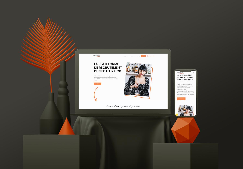 Macbook et iPhone noirs allumés avec la page internet ouverte sur le site HCR Emploi