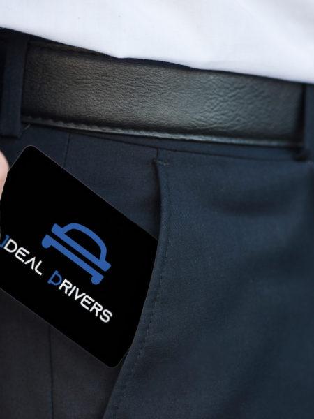 Carte de visite noire Ideal Drivers qui dépasse de la poche d'un homme