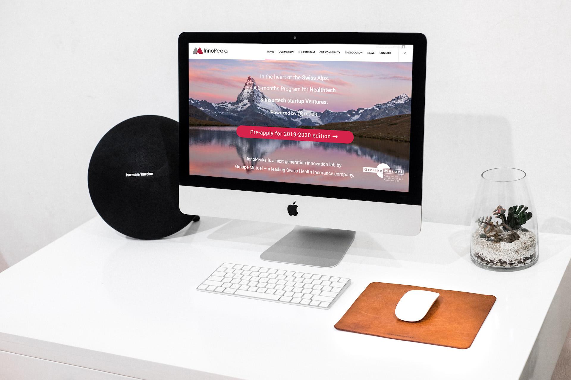 iMac posé sur un bureau allumé avec la page internet du site Innopeaks