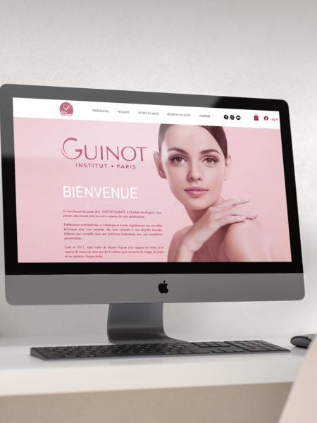iMac posé sur un bureau et allumé avec la page internet du site de l'Institut Guinot