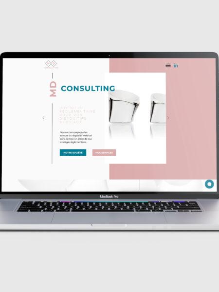 Macbook allumé avec la page internet du site de MD Consulting