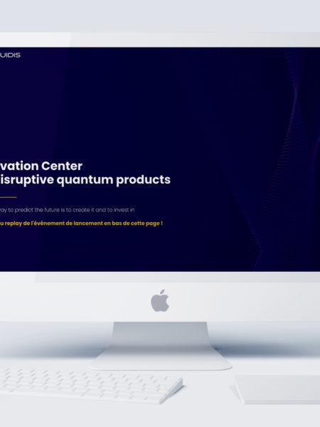 iMac blanc posé sur un bureau et allumé avec la page internet du site Naquidis