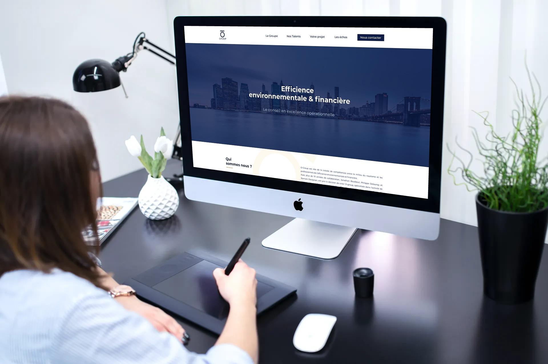 iMac allumé avec la page internet du site O-Group