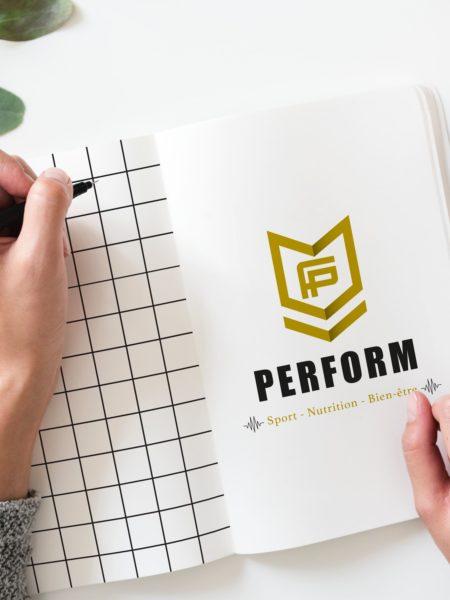 Femme dessinant un logo Perform dans un cahier